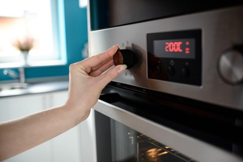 κοντινή λήψη στο χέρι γυναίκας η οποία ρυθμίζει τη θερμοκρασία στο φούρνο