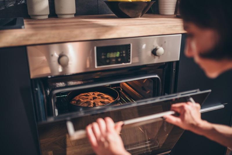 γυναίκα ανοίγει το φούρνο για να δει αν ψήθηκε το κέικ