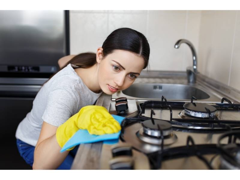 Γυναίκα καθαρίζει με γάντια επιφάνεια φούρνου με υγραέριο