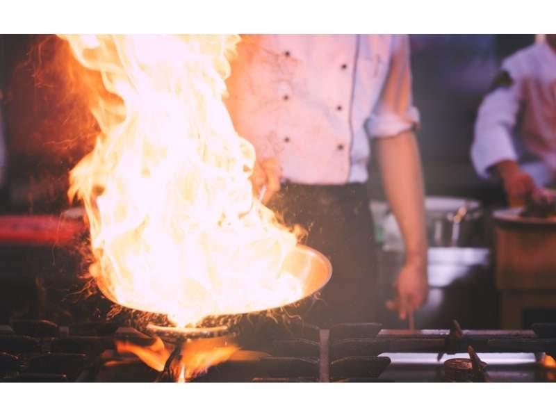 Μάγειρας κρατάει τηγάνι με φλόγα