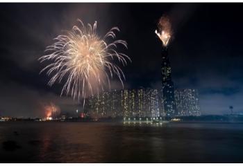 Πυροτεχνήματα νύχτα πίσω από φωτεινούς ουρανοξύστες