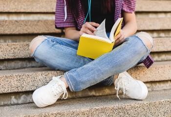 Έφηβη διαβάζει βιβλίο σε σκαλιά